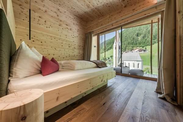 schlafzimmer_mit_bergblick_in_der_panoramasuite_naturhotel_rainer